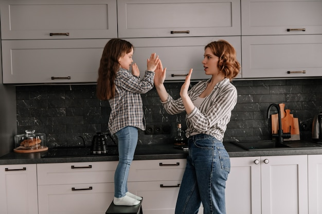 Mom and daughter clap their hands and pose in kitchen.