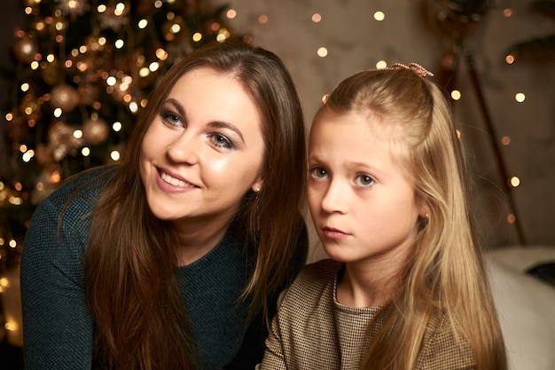Mom and daughter on a dark background with a garland