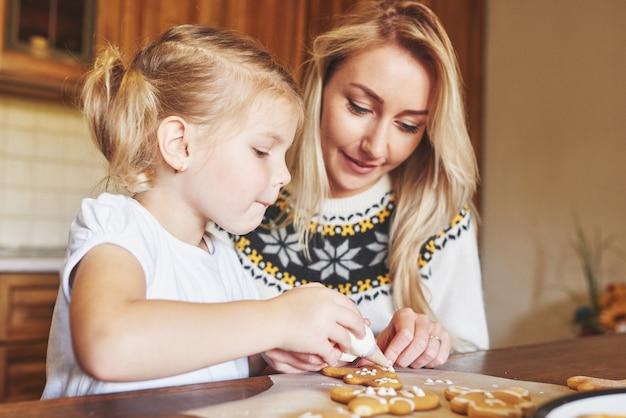 Mamma e figlia decorano il biscotto di natale con zucchero bianco
