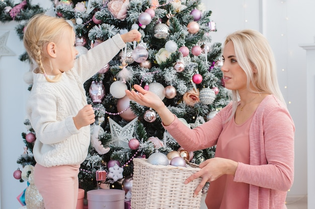 Mom and daughter decorate the christmas pink tree indoors.