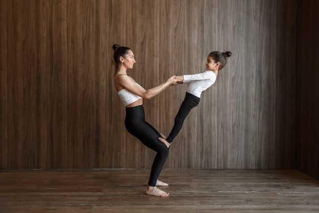 Mom and daughter doing yoga exercise together in the gym