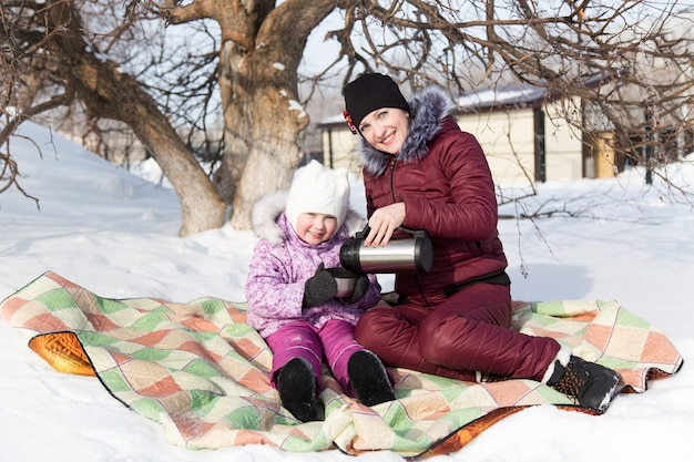 Mom and daughter drink tea from a thermos on a picnic.