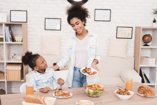 Mom and daughter eat together in the kitchen.
