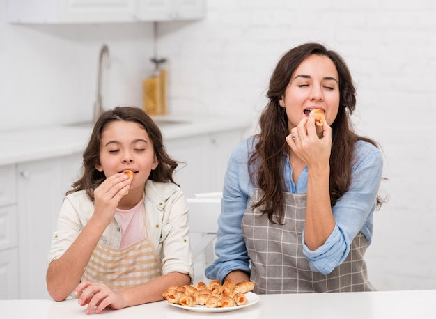Mom and daughter eating some pastries together