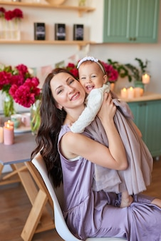 Mom and daughter in elegant dresses in the kitchen, decorated with peonies