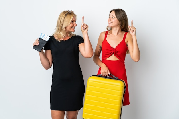 Mom and daughter going to travel isolated on white wall intending to realizes the solution while lifting a finger up