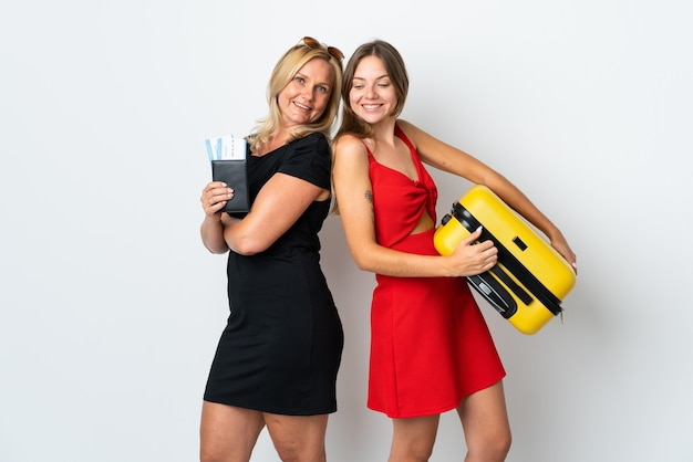 Mom and daughter going to travel isolated on white wall looking over the shoulder with a smile