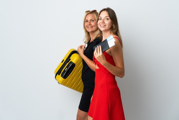 Mom and daughter going to travel isolated on white wall