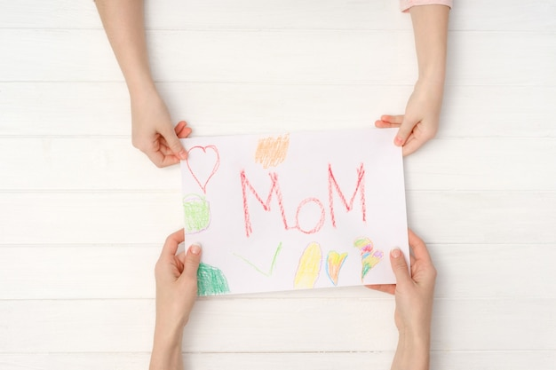 Mom and daughter hands holding colorful diy postcard with word mom written on it. lovely handmade card for mothers day or march 8 ot birthday