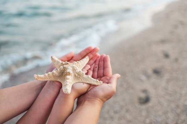 Mom and daughter in the hands holding a starfish on a background of the sea