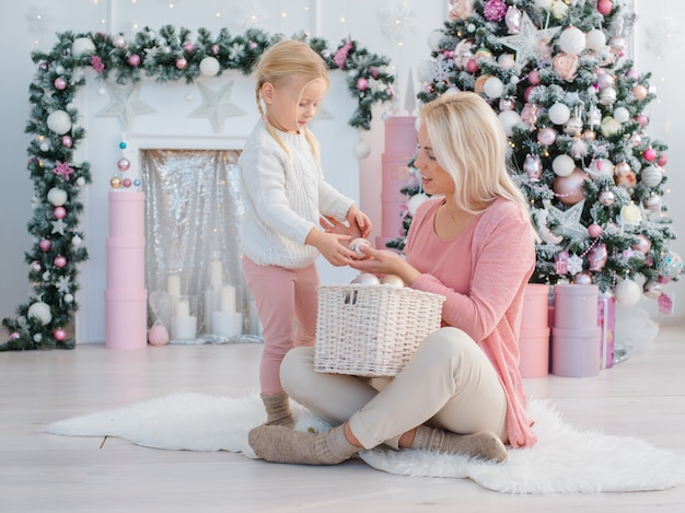 Mom and daughter have fun on the background of the christmas tree preparing for the holiday