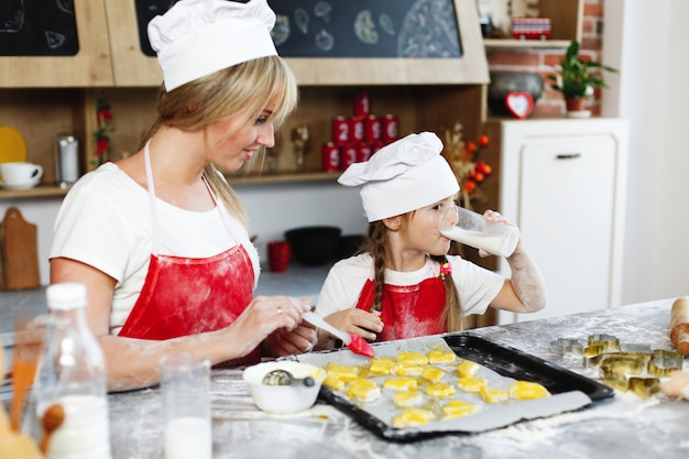 Mom and daughter have fun preparing cookies with milk at a dinner table in cosy kitchen