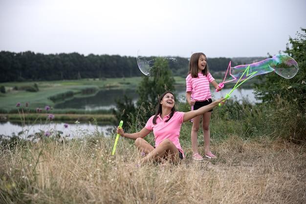 Mamma e figlia si divertono insieme, fanno grandi bolle di sapone, attività ricreative all'aperto.