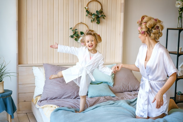 Mom and daughter having fun on the bed