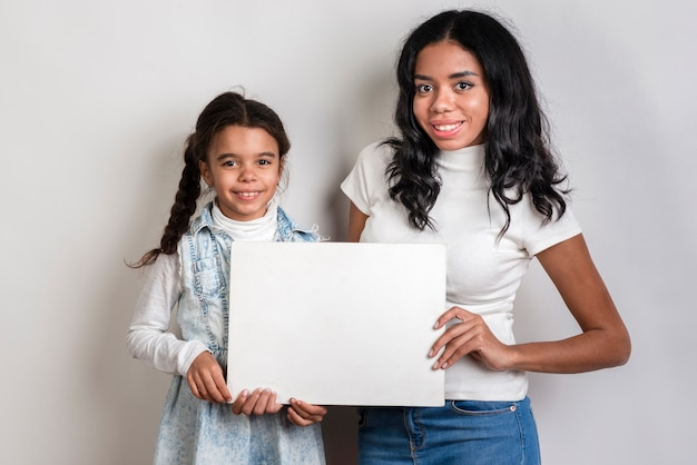 Mom and daughter holding blank paper