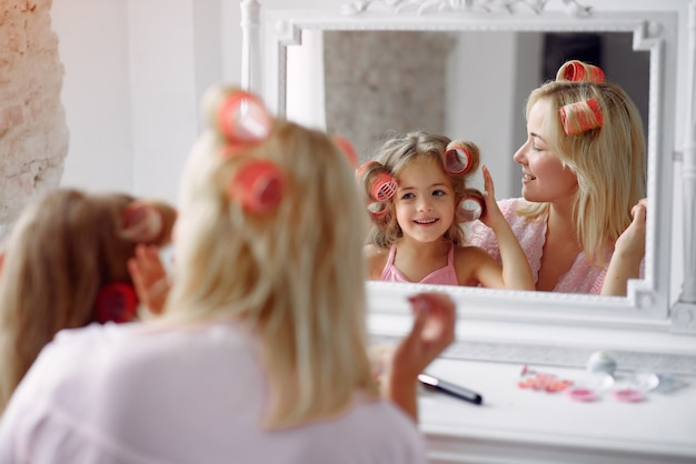 Mom and daughter at home with curlers on their heads