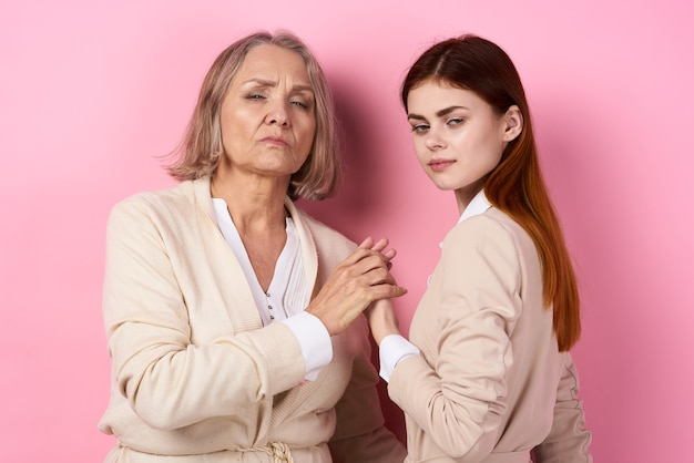 Mom and daughter hug together family caring pink background. high quality photo