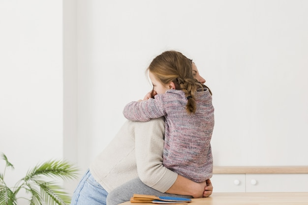 Mom and daughter hugging side view