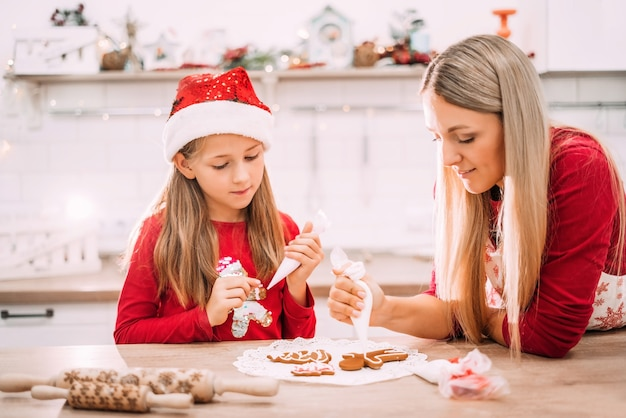 Mom and daughter in the kitchen glaze on gingerbread cookies in red sweaters and santa hats with lights in the background.
