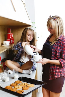 Mom and daughter on a kitchen taste together fresh baked chocolate cookies with milk