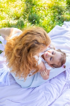 Mom and daughter laughing and hugging sitting on a blanket in the park the concept of a happy family...