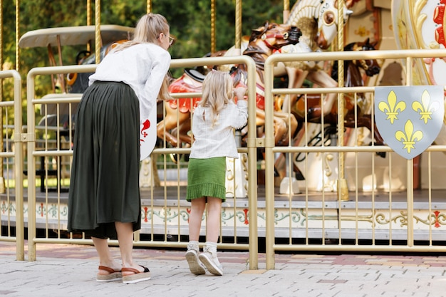 Mom and daughter look at the carousel in the park in the summer