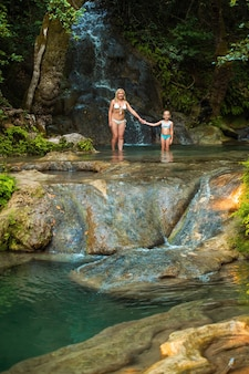 Mom and daughter on a mountain river under a waterfall in the jungle.turkey