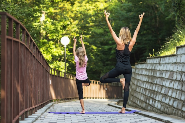Mom and daughter perform vrikshasana exercise in the park with raised arms tree pose