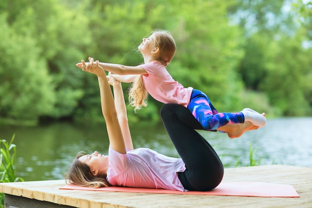 Mom and daughter perform a yoga exercise on the river bank on a warm sunny day