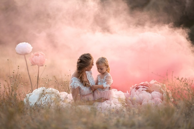 Mom and daughter in pink fairy-tale dresses are sitting in a field surrounded by big pink decorative flowers