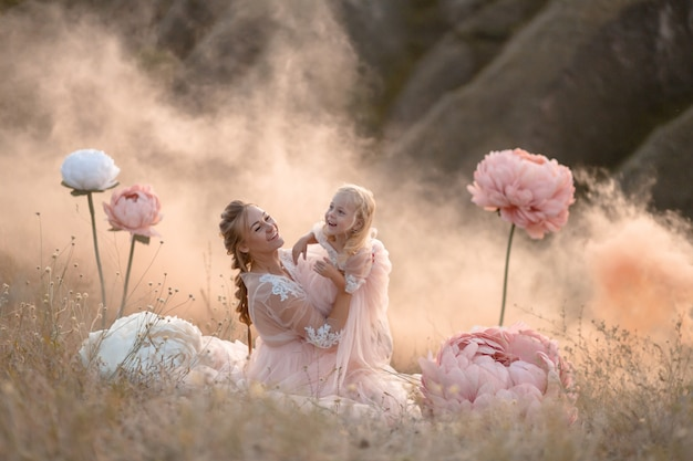 Mom and daughter in pink fairy-tale dresses play in a field