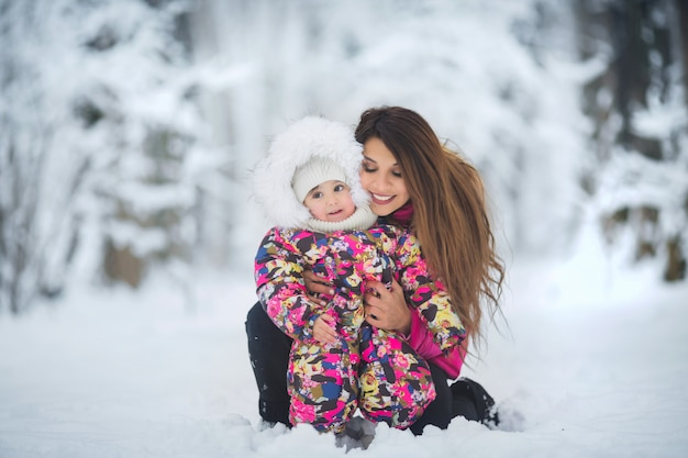 Mom and daughter in pink winter jackets walking in the winter forest among the snow