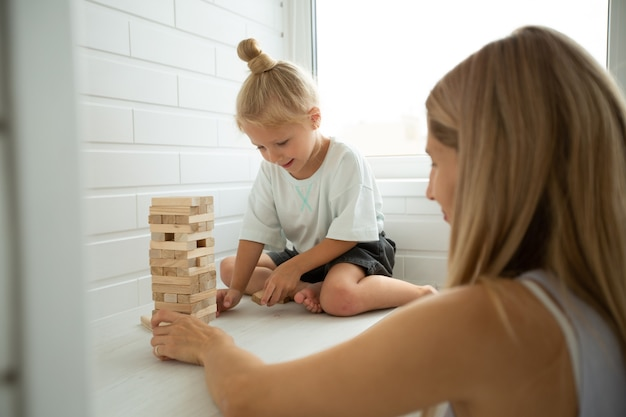 Mom and daughter play jenga at home