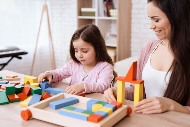 Mom and daughter play together with wooden cubes.