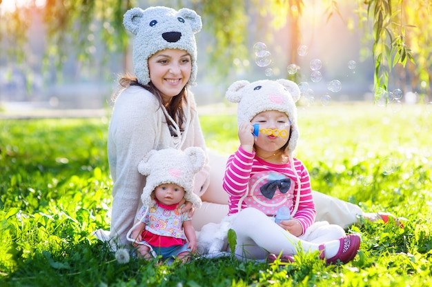 Mom and daughter playing in the park with a doll in caps