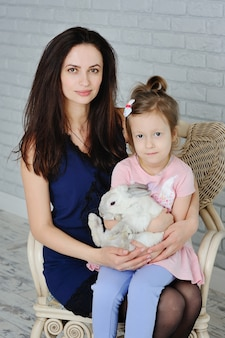 Mom and daughter playing with rabbit