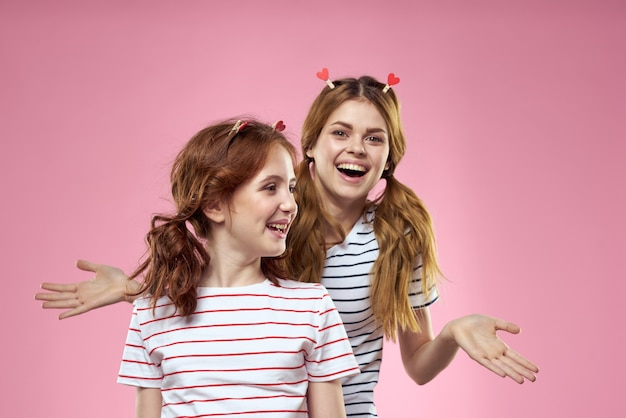 Mom and daughter  posing have fun and smile, happy family, two sisters, hearts and pink wall