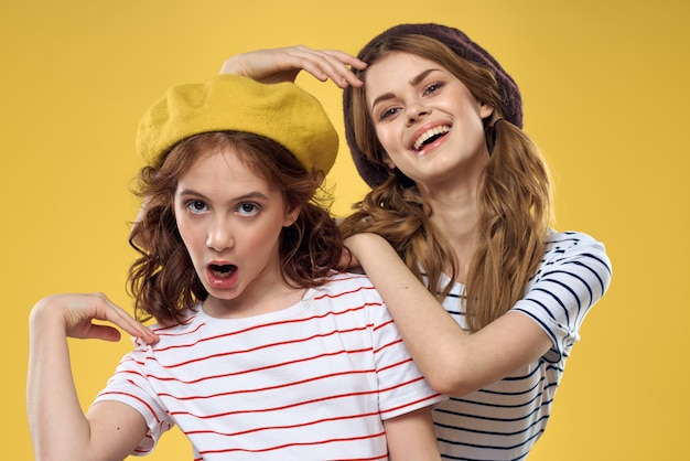 Mom and daughter posing have fun and smile, happy family, two sisters, the image of france and paris, berets on her head