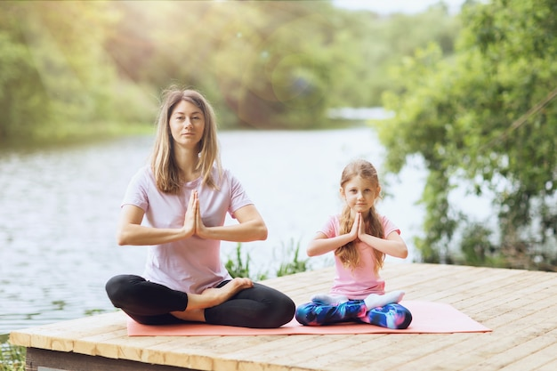 Mom and daughter practice yoga asanas on the river bank on a warm sunny day