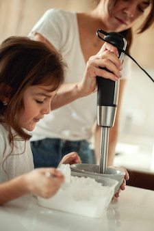 Mom and daughter prepare icing for gingerbread in their home kitchen. beat with a blender. the girl