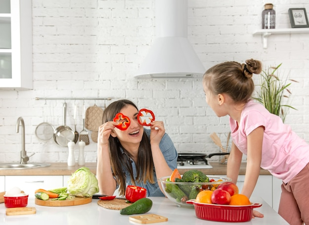 Mom and daughter prepare a salad in the kitchen. have fun and play with vegetables . the concept of a healthy diet and lifestyle.vegan nutrition and a healthy lifestyle.