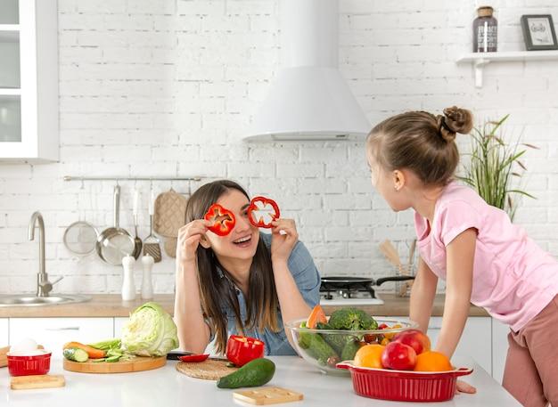 Mamma e figlia preparano un'insalata in cucina. divertiti e gioca con le verdure. il concetto di una dieta e uno stile di vita sani. nutrizione vegana e uno stile di vita sano.