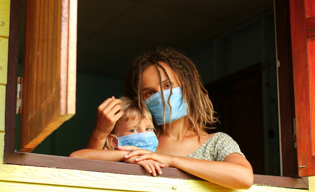 Mom and daughter in quarantine mask at home in isolation