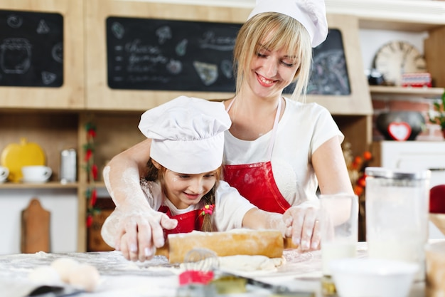 Mom and daughter in the same clothes have fun preparing a dough on a cosy kitchen
