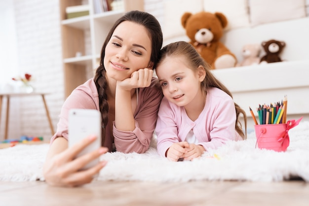 Mom and daughter do selfie on a smartphone.