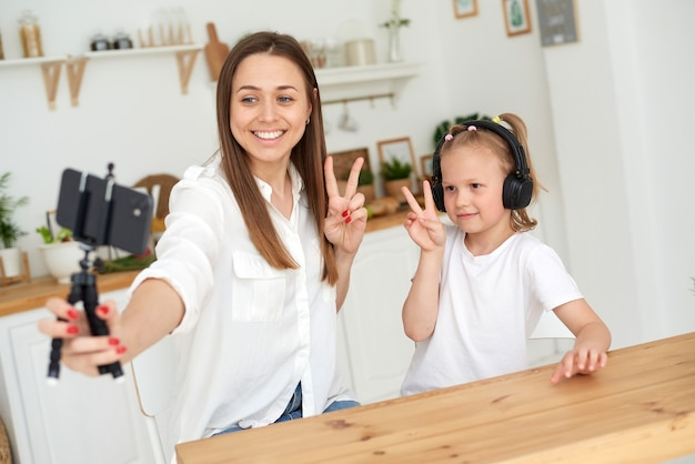 Mom and daughter show peace gesture to the camera. writing a blog to a video platform.