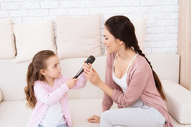 Mom and daughter sing songs at home.
