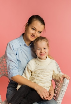 Mom and daughter sit on a chair and hug on a pink background
