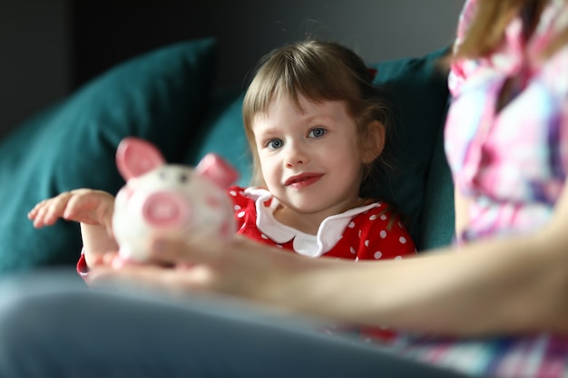 Mom and daughter sit home on couch with piggy bank