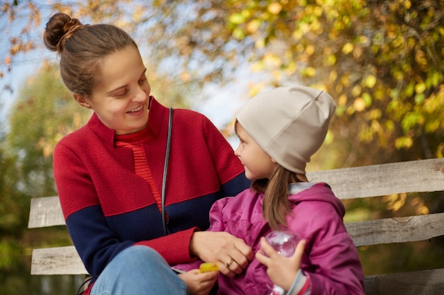 Mom and daughter sitting on a bench in nature by river, looking at each other with gentle smile
